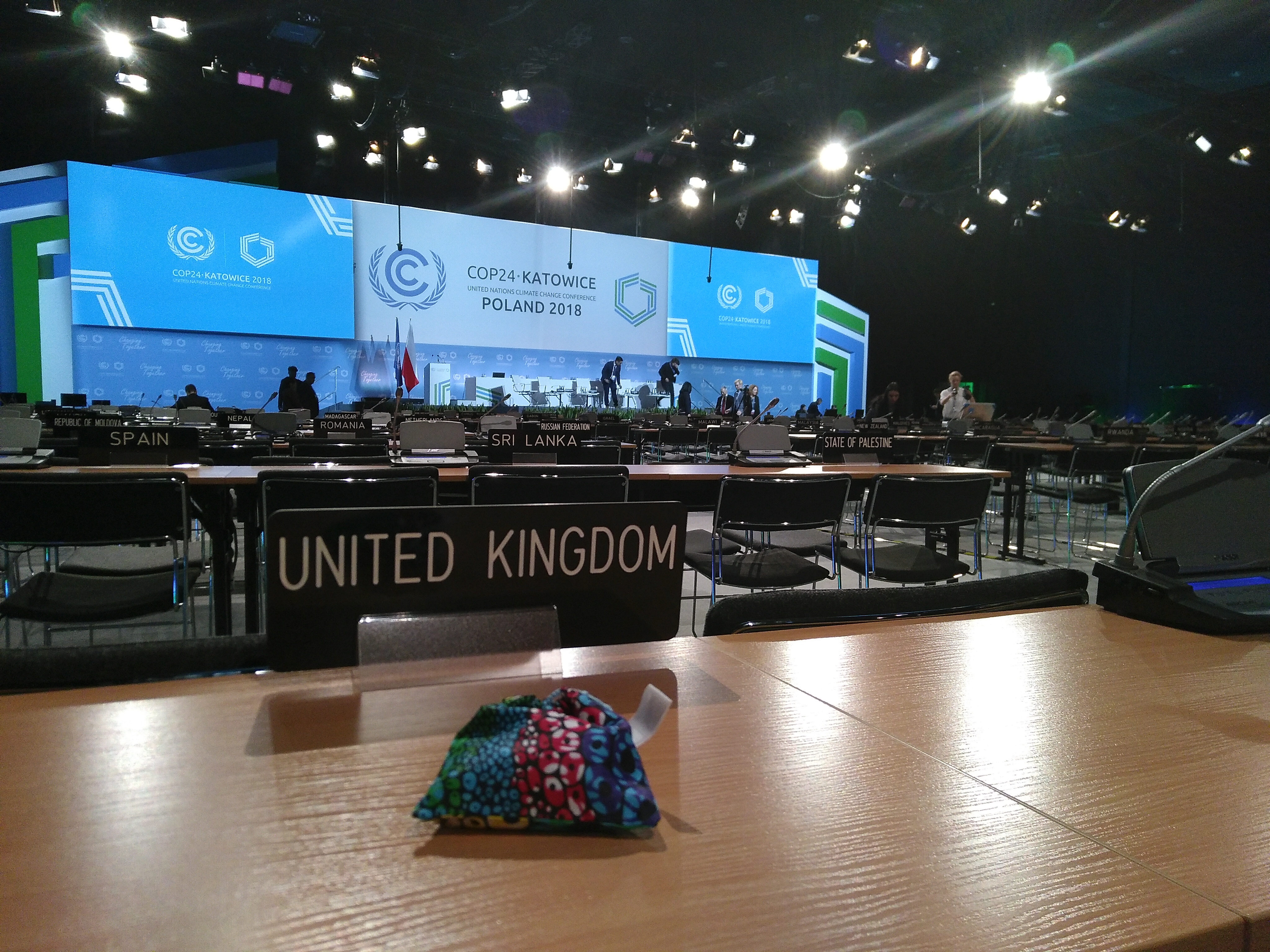 A fabric bag on a desk in a large conference room of tables, chairs, screens. The bag is in front of a sign saying United Kingdom and you can see other countries in the distance.